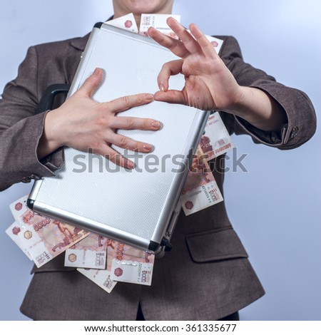 Woman in suit holds metal briefcase full of money - stock photo