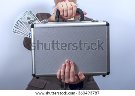 Woman in suit holds metal briefcase with dollars - stock photo