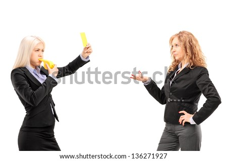 Woman in suit showing a yellow card and blowing a whistle to a female colleague, isolated on white background - stock photo