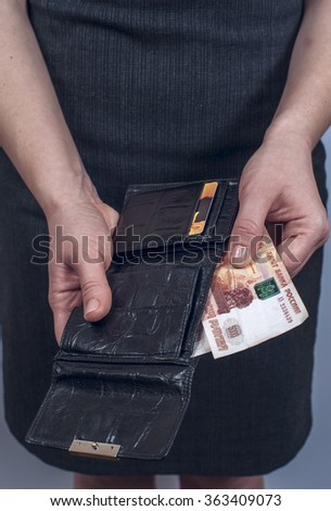 Woman in suit with leather purse full of money - stock photo