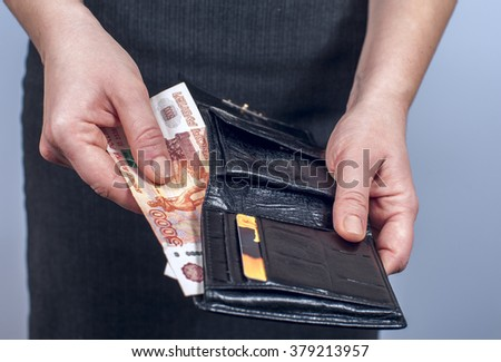 Woman in suit with leather wallet full of russian rubles. Conception of safe storage and protection of cash. Financial theme.  - stock photo