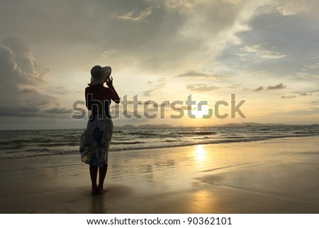Woman in summer dress standing on a sandy beach and looking to the sun - stock photo