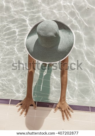 Woman in sun hat in the swimming pool. Top view. Vintage style. - stock photo