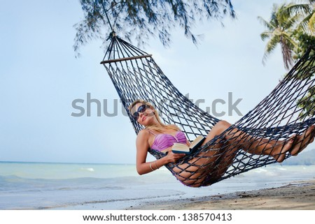 Woman in sunglasses and book relaxing in a hammock - stock photo
