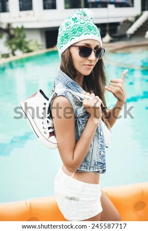 Woman in sunglasses and handmade denim vest . Outdoor lifestyle portrait of hipster girl showing hand gesture surfers - stock photo