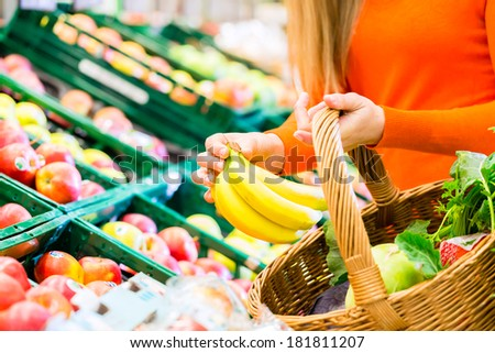 Woman in supermarket at the fruit shelf shopping for groceries, she is putting a banana in her basket - stock photo