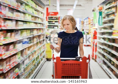 woman in supermarket, shopping - stock photo