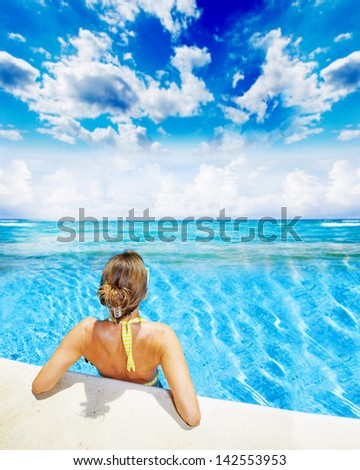 Woman in swimming pool at caribbean resort. Vacation. - stock photo