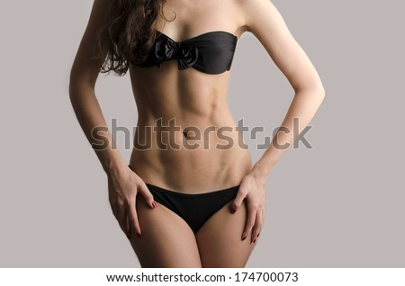 Woman in swimsuit with perfect abs, fit body - stock photo