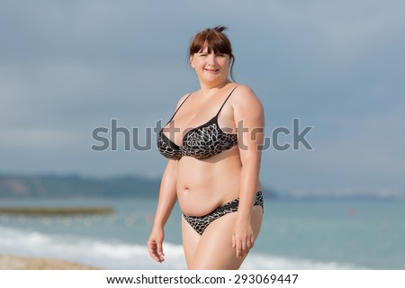 Woman in swimwear at the sea. Overweight young woman in swimsuit against the sea. She looking at camera smiling - stock photo