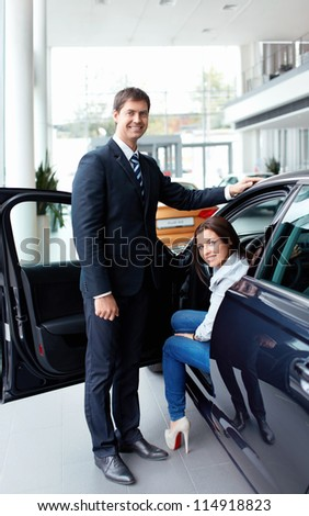 Woman in the car and seller at a showroom - stock photo