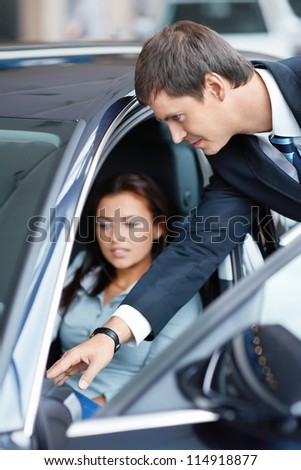 Woman in the car at a showroom - stock photo