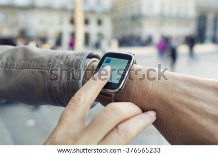 Woman in the city using her smartwatch. Blur Downtown background - stock photo