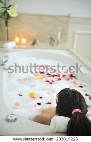 woman in the hot bath tub with flower petals in spa - stock photo