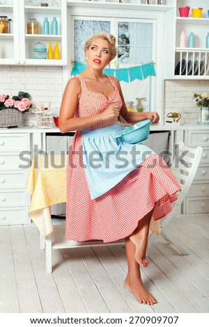 Woman in the kitchen is going to cook food. She wondered. Retro style. - stock photo