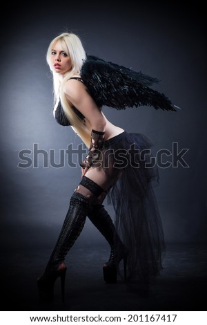 Woman in the lingerie with black angel wings against the black background - stock photo