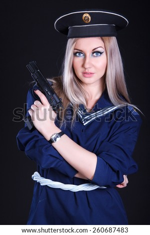 Woman in the marine uniform with a gun over black background - stock photo