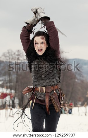 Woman in the medieval costume with a sword, vintage colors - stock photo