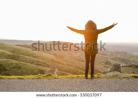Woman in the montains with open arms at the sunset - stock photo