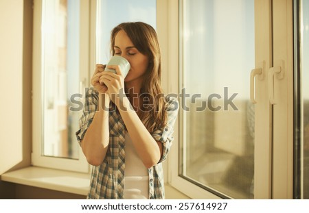 Woman in the morning. Attractive tender young woman is drinking hot tea or coffee from her cup and looking at the sunrise standing near the window in her home and having a perfect cozy morning.   - stock photo