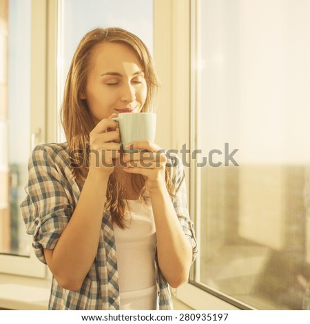 Woman in the morning. Attractive tender young woman is holding a cup with hot tea or coffee and looking at the sunrise standing near the window in her home and having a perfect cozy morning. - stock photo