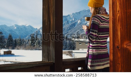 Woman in the morning. Young smiling woman enjoying sunny morning in the Alps mountains drinking tea or coffee on a balcony in the chalet house with a mountain view. - stock photo