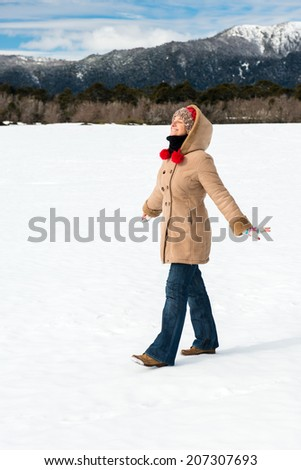 Woman in the snow enjoying the scenery - stock photo