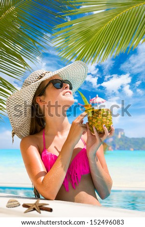 Woman in the swimming pool enjoying a fresh cocktail at luxury tropical resort in Thailand - stock photo