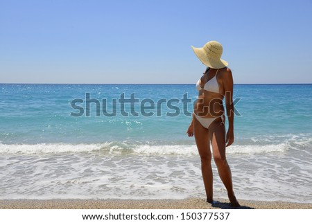 Woman in the white hat and the sea - stock photo