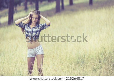 Woman in tight white jeans shorts and tied up blue flannel shirt posing with both hands up - stock photo