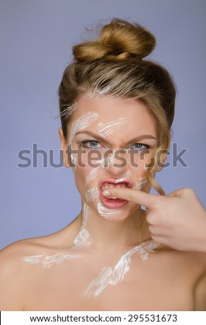 woman in toothpaste on body cleans finger teeth on blue background - stock photo