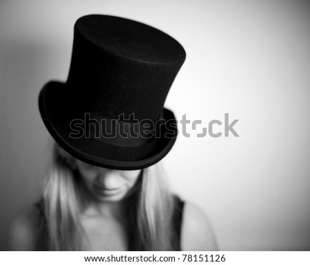 Woman in top hat looking down - stock photo