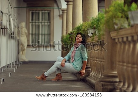 woman in trousers posing sitting in the balcony with antique stone pillars - stock photo