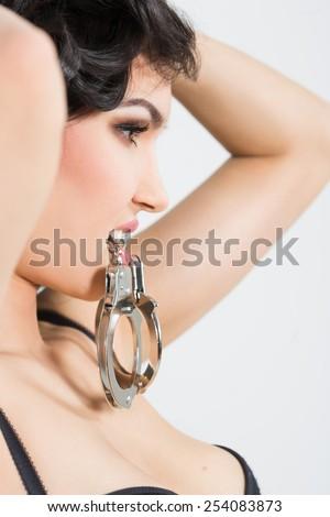 Woman in underwear, bite handcuffs, bdsm, sex toy - stock photo