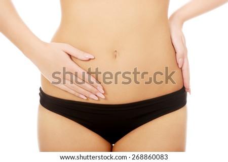 Woman in underwear touching her slim belly. - stock photo