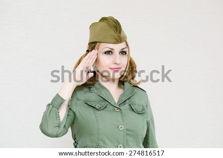 Woman in uniform gives military salute. Girl in garrison cap. In honor of Victory Day on May 9. - stock photo