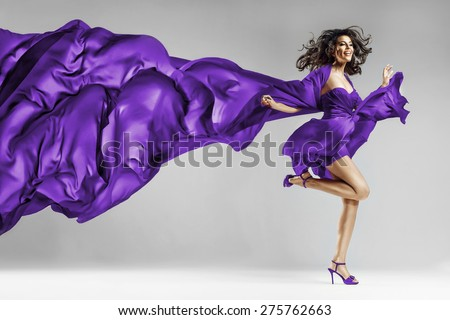 Woman in violet waving dress with flying fabric This photo has cut contours Dress! (in Photoshop) - stock photo