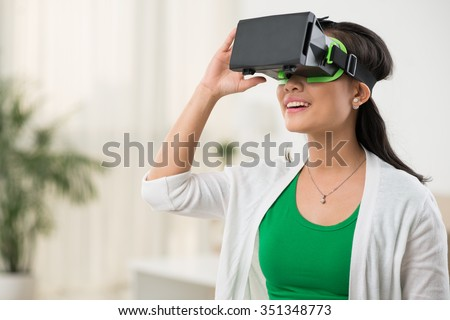 Woman in virtual reality glasses playing the game - stock photo