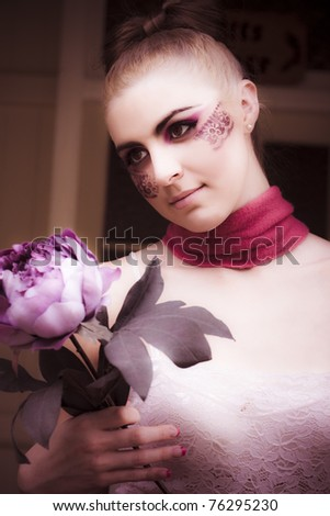 Woman In Vogue Style Makeup And Cosmetics Holds A Large Purple Flower Near The Front Door Of Her House Or Home In A Romantic And Love Present Conceptual - stock photo