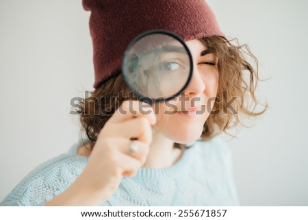 Woman in warm red winter hat and looking through the magnifying glass at blank copy space, over white - stock photo