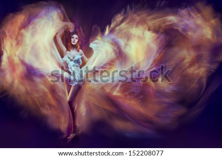 Woman in waving dress as a flame dancing with flying fabric. Dark background - stock photo