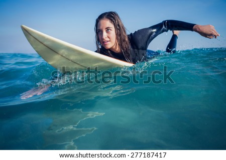 woman in wetsuit with a surfboard on a sunny day at the beach - stock photo