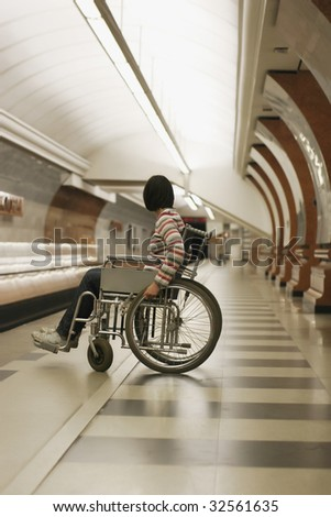 Woman in wheelchair in subway - stock photo