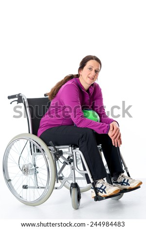 woman in wheelchair is  doing sport with ball  - stock photo