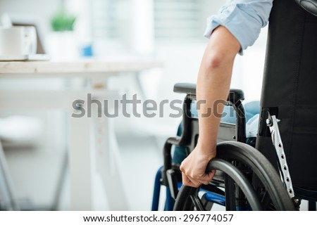 Woman in wheelchair next to an office desk, hand close up, unrecognizable person - stock photo