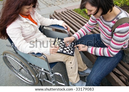 woman in wheelchair plays with girlfriend in a chess - stock photo