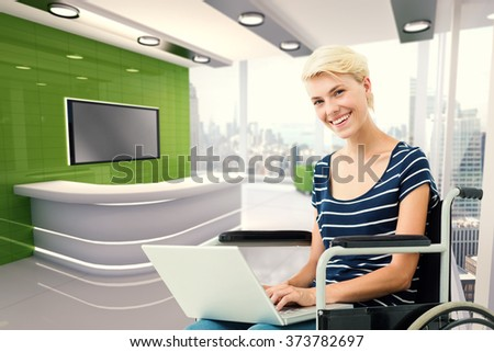 Woman in wheelchair using computer against modern room overlooking city - stock photo