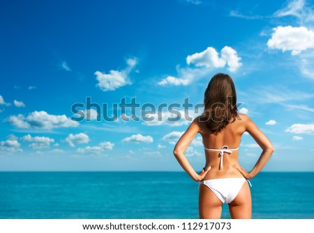 Woman in White Bikini at the Sea. Rear View. - stock photo