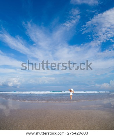 woman in white clothing refreshing at the ocean, bali Indonesia - stock photo