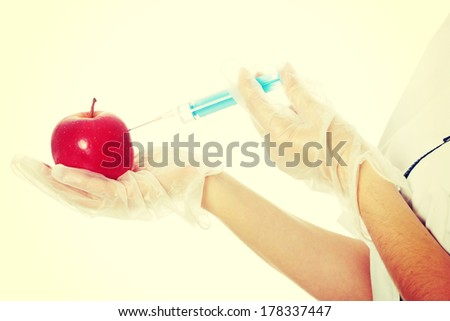 Woman in white coat with syringe and apple (biotechnologist). White background. Studio shot.  - stock photo